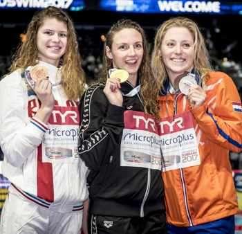 Призьорките в плуването на 100 м гръб позират с медалите си от европейското първенство в 25-метров басейн в Копенхаген (Дан). Унгарската звезда Катинка Хошу (в средата) триумфира с резултат 55,66 сек., следвана на 55 стотни от холандката Кира Тусен (вдясно) и на 1,35 сек. от рускинята Мария Каменева (вляво).