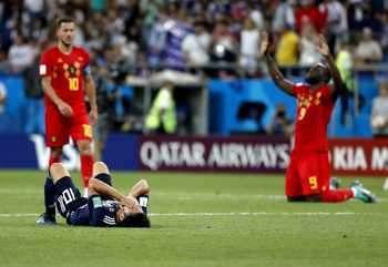 Японецът Шинджи Кагава лежи разстроен на тревата, докато край него капитанът на белгийците Еден Азар (вляво) се е запътил да се радва заедно с Ромелу Лукаку на победата в 1/8-финала в Ростов на Дон.
